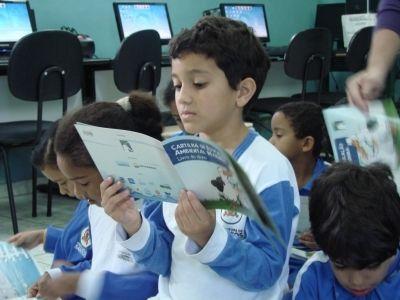"""Aluno da escola Martins Fontes lendo o """"Livro do Aluno"""", cartilha de educação ambiental marinha do Projeto Albatroz"""