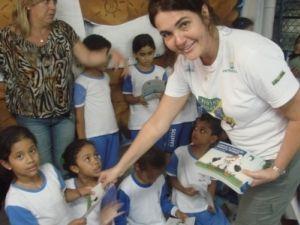 Maria Claudia Kohler, coordenadora de Educação Ambiental do Projeto, entregando as cartilhas de educação ambiental marinha do Projeto