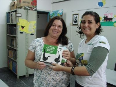 Cynthia Ranieri, assistente de Educação Ambiental do Projeto, entregando cartilha à escola Padre Leonardo Nunes