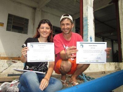 Cassiane Tatsch, estagiária do Projeto Albatroz, entregando certificado de capacitação ao pescador