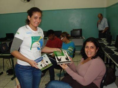 Cynthia Ranieri, do Projeto Albatroz, entrega cartilhas à professora da escola municipal Martins Fontes